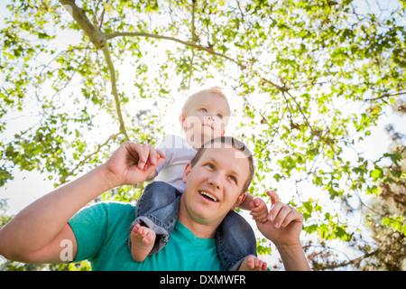 Jeune garçon mignon Piggyback Rides sur ses pères épaules à l'extérieur du parc. Banque D'Images