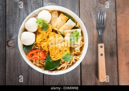 Curry épicé nouilles potage instantané avec la fourchette sur la table à manger en bois. Douce chaude avec de la Banque D'Images