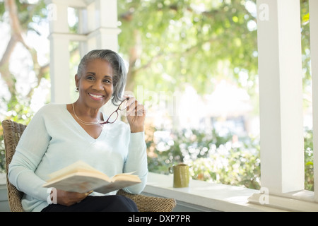 Portrait of smiling senior woman reading book on porch Banque D'Images