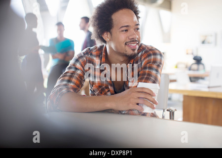 Creative businessman drinking coffee in office Banque D'Images