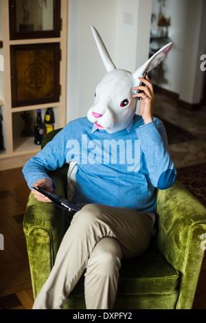 Le multitâche d'affaires élégant masque de lapin à l'aide d'appareils à la maison de l'homme Banque D'Images
