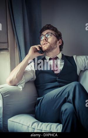 Mode attrayant élégant hipster homme au téléphone à la maison Banque D'Images