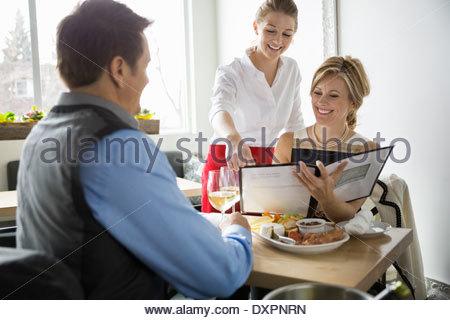 Aider l'ordre à partir de la serveuse femme menu dans le bistro Banque D'Images