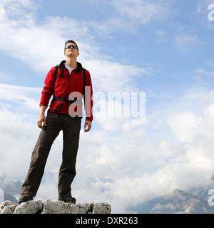 Un jeune alpiniste de profiter de son succès sur le sommet d'une montagne Banque D'Images