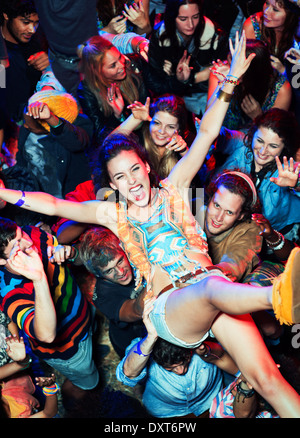 Femme enthousiaste crowd surfing at music festival Banque D'Images