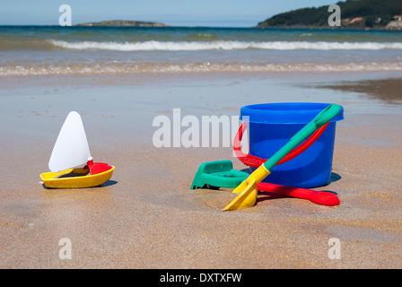 Jouets en plastique colorés: un seau , plage rake et spade avec bateau sur une plage Banque D'Images