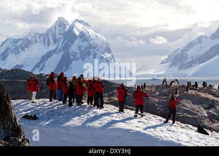 L'antarctique le tourisme avec les passagers des bateaux de croisière antarctique manchots de visualisation et la montagne, paysage montagneux. Banque D'Images