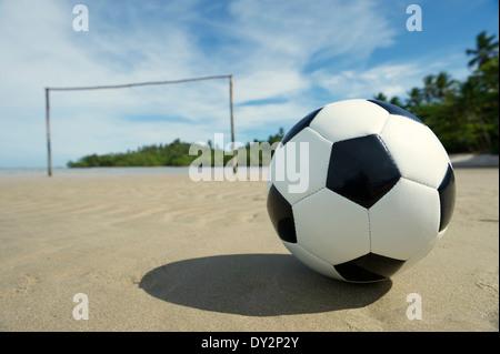 Soccer ball assis sur de simples brésilien de football avec des poteaux de but rustique qui sort du sable
