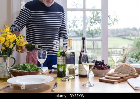 L'homme verse du vin à l'heure du déjeuner avec dégustation Banque D'Images