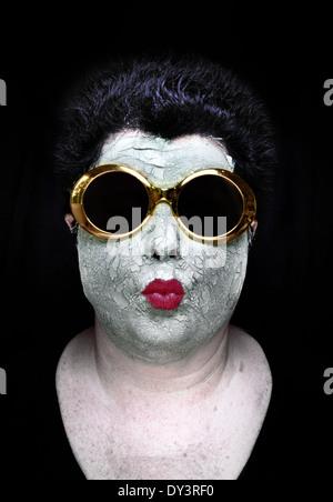 Une femme portant un masque de boue vert, rouge à lèvres rouge, et fantasque lunettes or fronce ses lèvres Banque D'Images