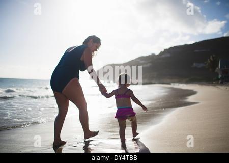 Mère et fille se tenir la main, marcher dans la mer Banque D'Images
