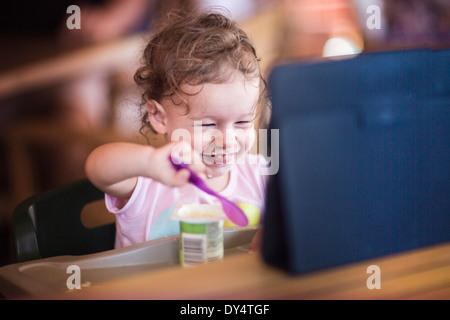 Toddler eating yoghurt and using digital tablet Banque D'Images