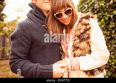 Couple holding hands laughing, cropped Banque D'Images