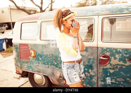 Femme par retro campervan laughing Banque D'Images