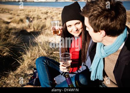 Couples célébrant avec du vin blanc à l'autre, Bournemouth, Dorset, UK Banque D'Images