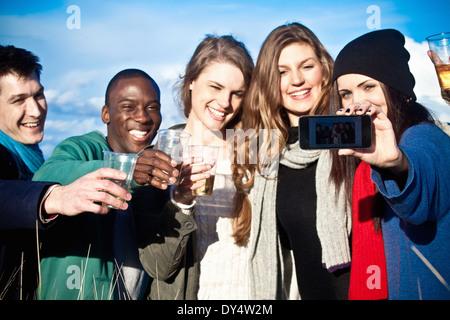 Young adult friends toasting avec vin blanc et en tenant selfies Banque D'Images