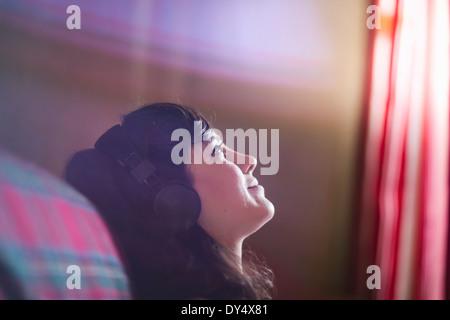 Jeune femme portant des écouteurs, daydreaming