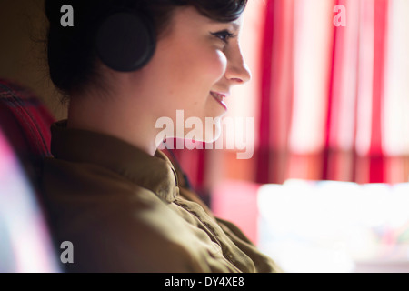 Jeune femme assise sur un canapé, listening to music on headphones Banque D'Images