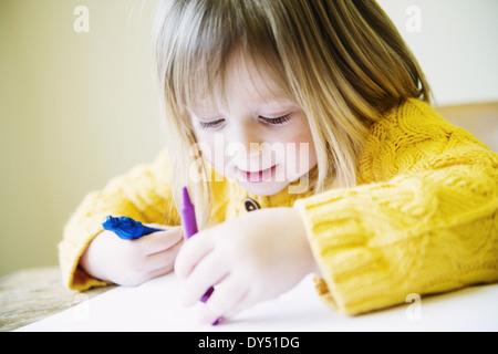 Jeune fille à la table de cuisine à colorier avec des feutres Banque D'Images