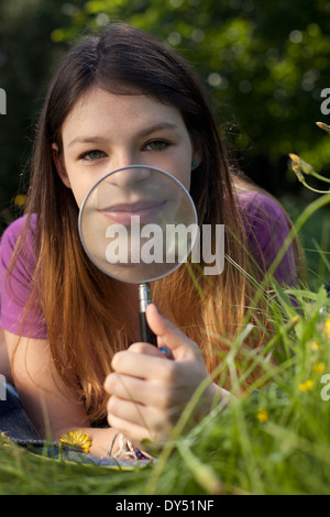 Teenage girl lying in grass brandissant une loupe pour sa bouche Banque D'Images
