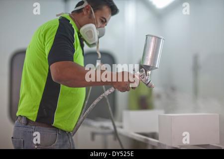 La pulvérisation de produits en bois homme in carpenters workshop Banque D'Images