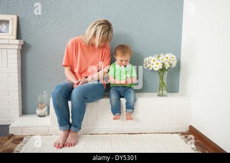 Jeune femme et bébé Garçon jouant avec des fleurs Banque D'Images