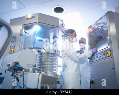 Les travailleurs ayant comprimé appuyant sur la machine en usine pharmaceutique Banque D'Images