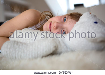Furry Girl lying on bed with teddy bear Banque D'Images