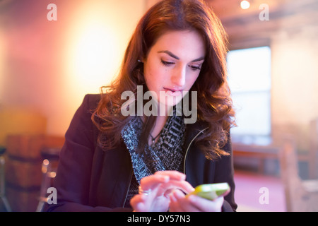 Young woman texting on smartphone in cafe Banque D'Images