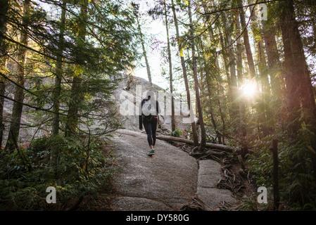Jeune femme marchant à travers la forêt, Squamish, British Columbia, Canada