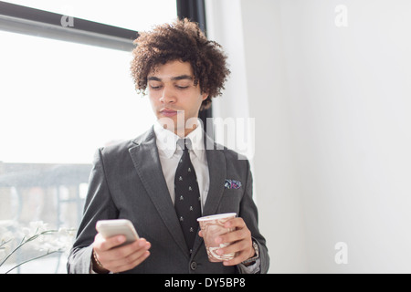 Young man using cell phone with coffee Banque D'Images
