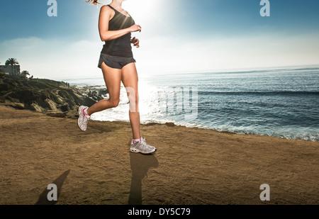 Mid adult woman jogging le long de falaise Banque D'Images