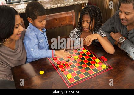 Couple et enfants jouant à table à manger Banque D'Images