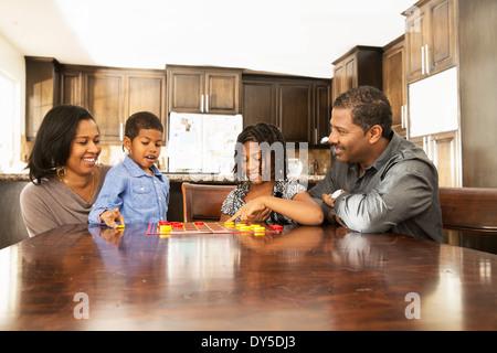 Couple et enfants jouant à table brouillons Banque D'Images