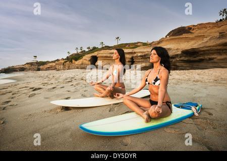 Deux surfeurs, assis sur des planches de surf sur la plage, méditant Banque D'Images
