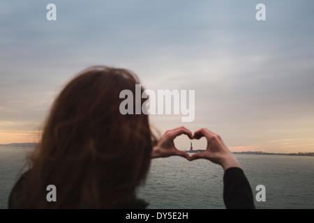 Jeune femme en forme de coeur autour de la statue de la liberté, New York, USA Banque D'Images
