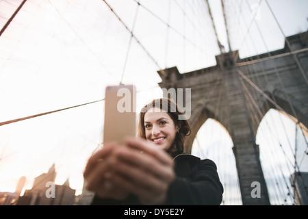 Jeune femme prenant sur selfies pont de Brooklyn, New York, USA Banque D'Images