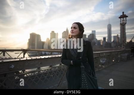 Jeune femme se promenant sur le pont de Brooklyn, New York, USA Banque D'Images