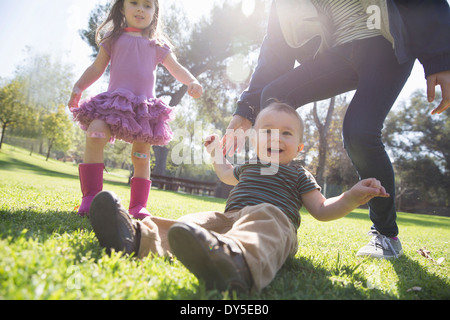 Siblings playing in park Banque D'Images