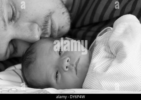 Le noir et blanc cropped shot de père couché avec son bébé nouveau-né fille de câlins Banque D'Images