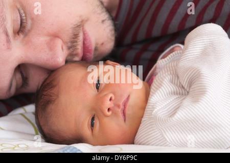 Cropped shot de père couché avec son bébé nouveau-né fille de câlins Banque D'Images