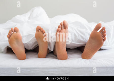 Des couples pieds qui sort d'une couette sous Banque D'Images