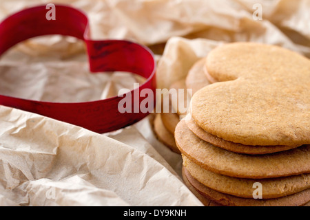 Emporte-pièce en forme de coeur rouge et un tas de brown Noël gingerbread cookies faits maison Banque D'Images