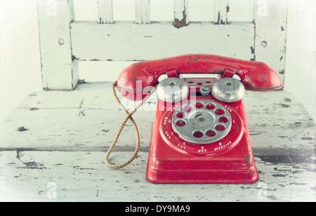 Téléphone jouet rouge sur la vieille chaise en bois bleu clair avec l'édition vintage Banque D'Images