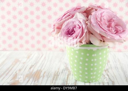 Roses roses dans un vase vert polkadot vintage sur fond shabby chic en bois blanc Banque D'Images