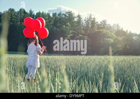 Petite fille avec un bouquet de ballons rouges à au coucher du soleil dans un paysage d'été vert avec l'édition Banque D'Images