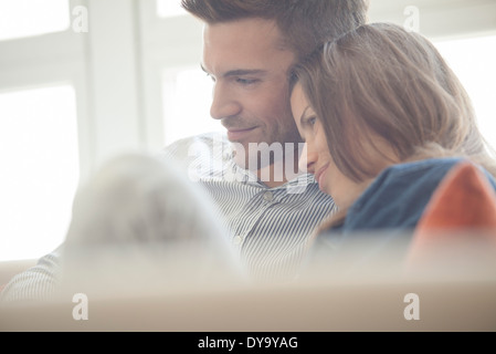 Couple relaxing at home looking at digital tablet Banque D'Images