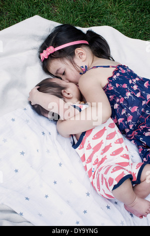 Little girl with baby brother lying on blanket outdoors Banque D'Images
