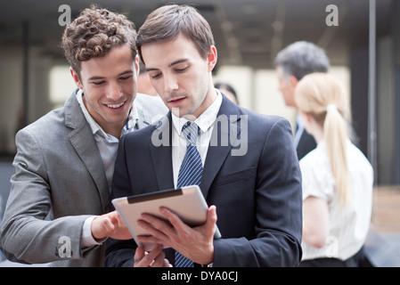 Businessman showing collègue digital tablet Banque D'Images