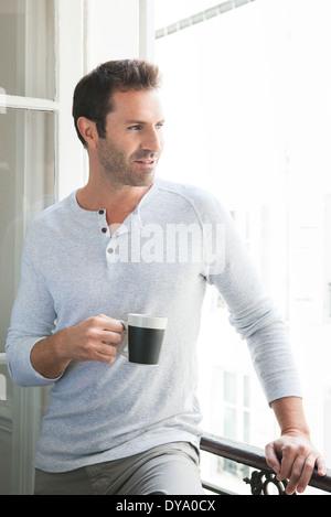 Man looking out de fenêtre avec mug dans la main Banque D'Images